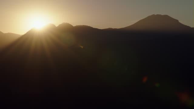vídeos de stock, filmes e b-roll de the peaks of lassen volcanic national park silhouetted against the sky at dawn. - ponto de referência natural