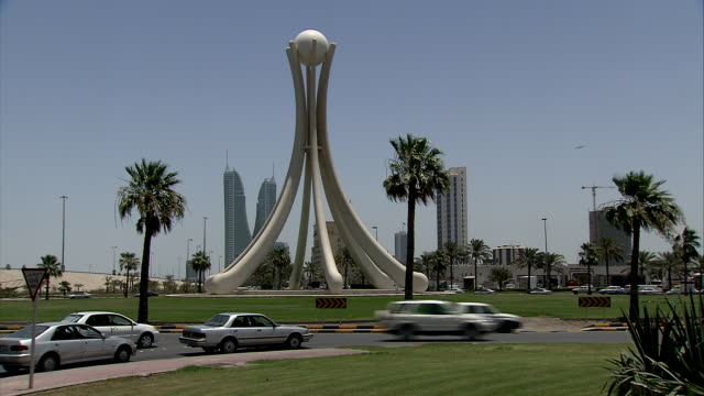 WS The Pearl Monument with Bahrain Financial Harbor skyline beyond and vehicle traffic negotiating the Pearl Roundabout / Manama, Bahrain