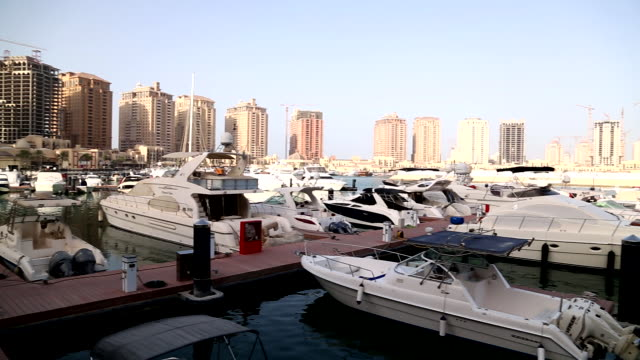 the pearlqatar artificial manmade island highrise luxury residential buildings in semicircle marina bridge docked boats yachts - semi circle stock videos & royalty-free footage
