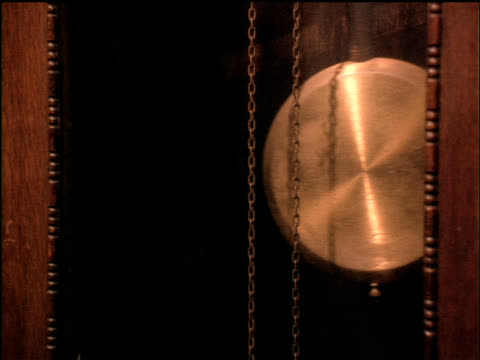 the pendulum on a grandfather clock swings back and forth. - schwingen stock-videos und b-roll-filmmaterial