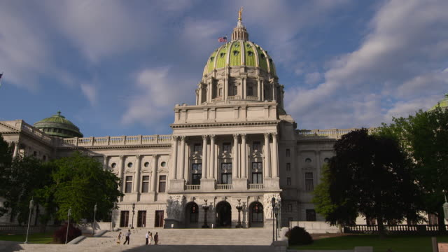 vídeos de stock, filmes e b-roll de the pennsylvania capital building in harrisburg pa early evening.  people walking up the steps. - legislação