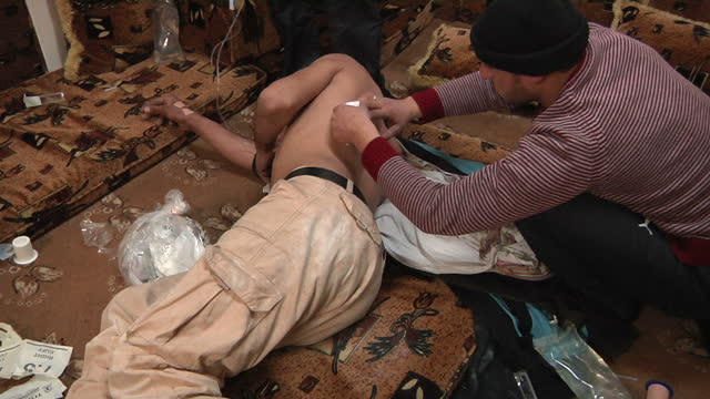 The people of Homs are under siege from Assad's forces Shows interior shots injured man having his wounds treated by people in makeshift hospital on...