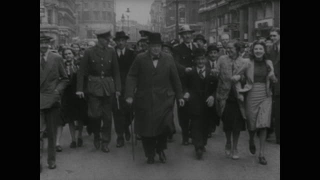 vídeos de stock, filmes e b-roll de the people of london cheer as they walk alongside prime minister winston churchill in the aftermath of the blitz, death and destruction all around - forças aliadas