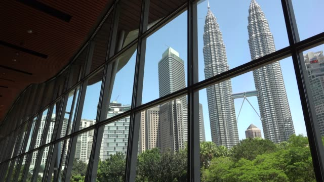 the petronas towers are twin skyscrapers in kuala lumpur malaysia according to the council on tall buildings and urban habitat's official definition... - petronas twin towers stock-videos und b-roll-filmmaterial