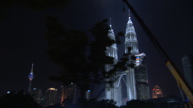 the petronas towers glow in the cityscape of kuala lumpur, malaysia. - petronas twin towers stock-videos und b-roll-filmmaterial