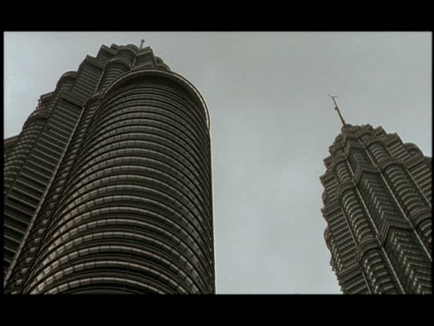 the petronas towers rise into a cloudy sky. - turmspitze stock-videos und b-roll-filmmaterial