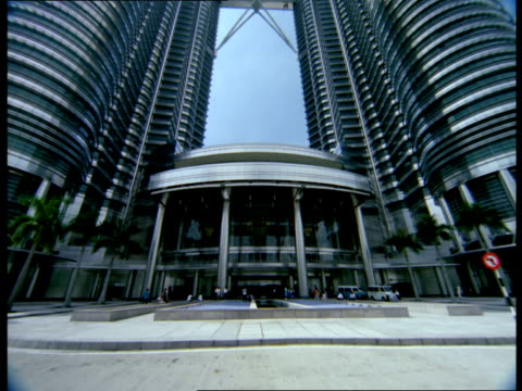 the petronas towers stretches to the sky in kuala lumpur, malaysia. - petronas twin towers stock videos and b-roll footage