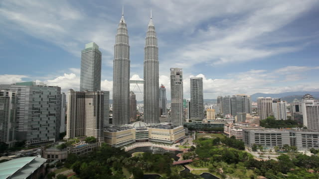 The Petronas Towers tower over surrounding buildings in Kuala Lumpur, Malaysia.
