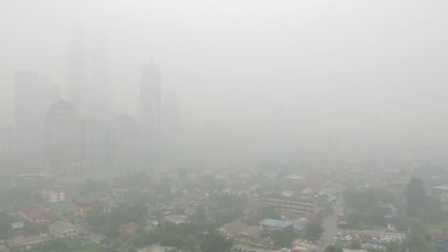 The Petronas Twin Towers rear left stand shrouded in haze in Kuala Lumpur Malaysia on Monday Oct 19 Buildings stand shrouded in haze in the Kampung...
