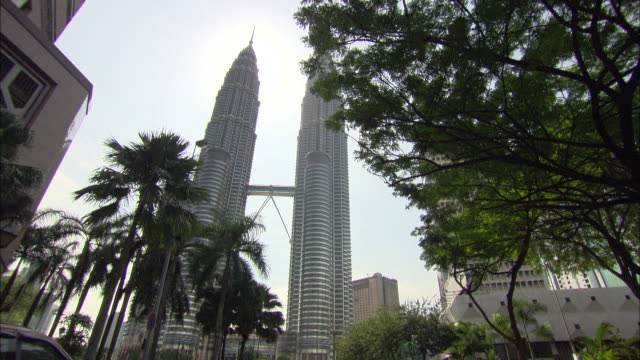 the petronas twin towers soar in downtown kuala lumpur. - kuala lumpur stock videos & royalty-free footage