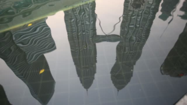 The Petronas Twin Towers stand in Kuala Lumpur Malaysia on Monday July 21 The Petronas Twin Towers are reflected in a pool of water in Kuala Lumpur...