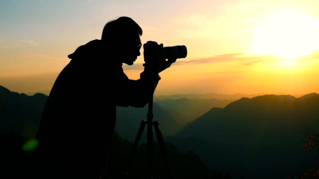 the photographer shot the mountain sunset - fotografo video stock e b–roll