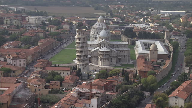 the piazza dei miracoli features the spectacular leaning tower of pisa and the cathedral of pisa in pisa, italy. - pisa cathedral stock videos & royalty-free footage