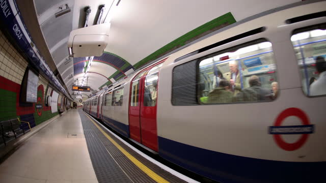 the piccadilly line arrives at piccadilly circus tube station and passengers depart in the london underground. - london underground stock videos & royalty-free footage