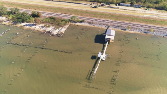 The pier and railroad along of the shore of the Lake Pontchartrain, New Orleans, Louisiana, USA. Accelerated aerial drone video with the tilting-up camera motion.