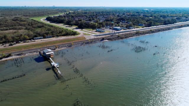 The pier and railroad along of the shore of the Lake Pontchartrain, New Orleans, Louisiana, USA. Aerial drone video with the forward camera motion.