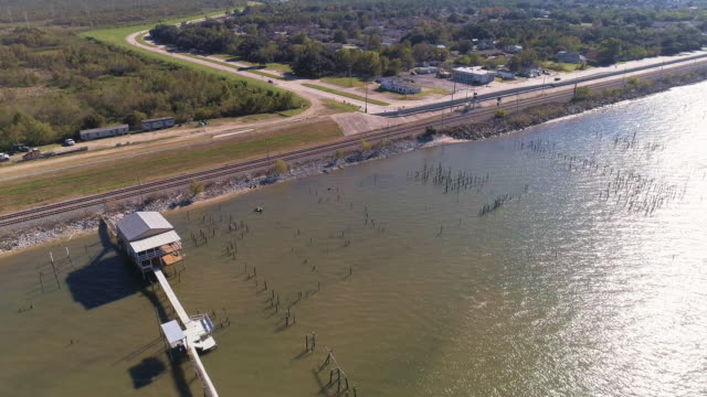 The pier and railroad along of the shore of the Lake Pontchartrain, New Orleans, Louisiana, USA. Aerial drone video with the cinematic panoramic, forward and tilting-down complex camera motion.