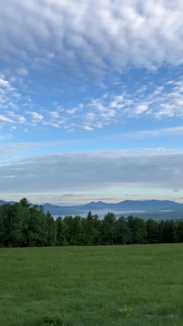 The Pilot Mountain Range and grassy meadow at dawn viewed from Cates Hill drive in Berlin, NH 2019