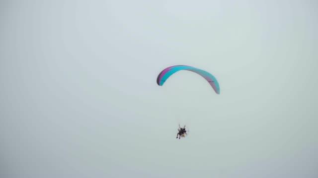 パラグライダーパラモーターのパイロットが浜辺を飛んでいる。 - パラグライディング点の映像素材/bロール