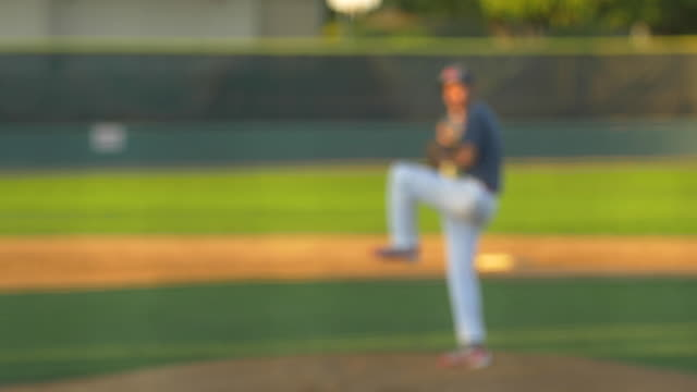 the pitcher at a baseball game throws the ball to the batter. - slow motion - baseball pitcher stock videos and b-roll footage