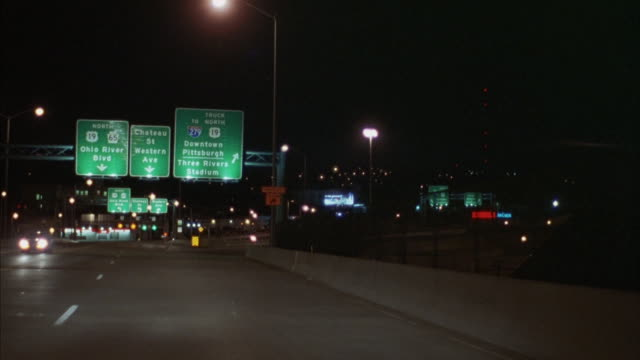 the pittsburgh skyline glows off of the freeway. - pittsburgh video stock e b–roll