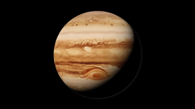 The planet Jupiter rotates in black space.