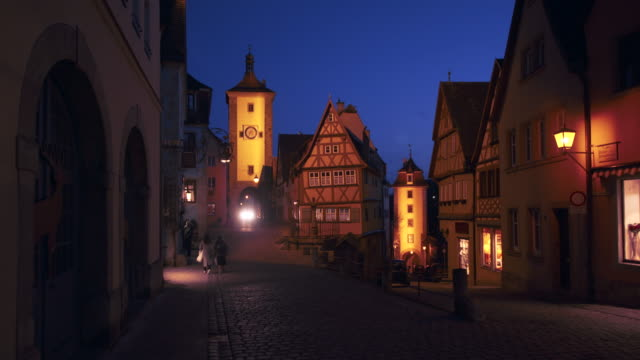 the ploenlein with sieber tower and kobolzeller tower illuminated at dusk twilight. - rothenburg stock videos and b-roll footage