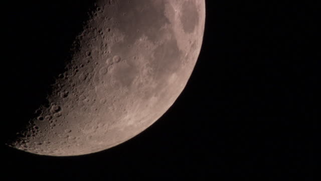 the pocked surface of a half moon is visible in a dark sky. - moon stock videos & royalty-free footage