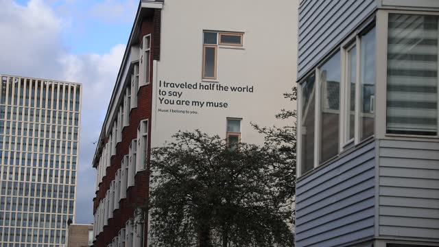 the poetic message 'i travelled half the world to say you are my muse. muse i belong to you' is written on the facade of a building in the city... - wall building feature stock videos & royalty-free footage