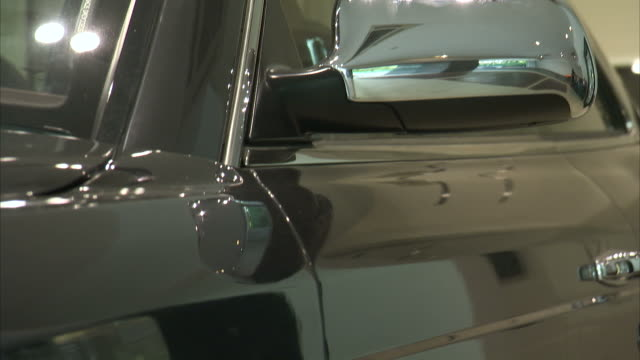 the polished side of a luxury car in a dealership reflects a car dealership showroom. - metal stock videos & royalty-free footage