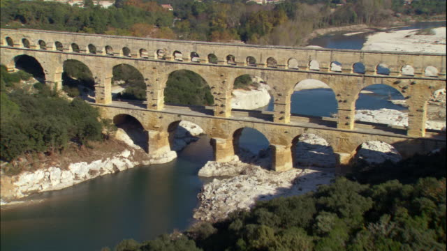 the pont du gard stretches over the gardon river. - aqueduct stock videos and b-roll footage