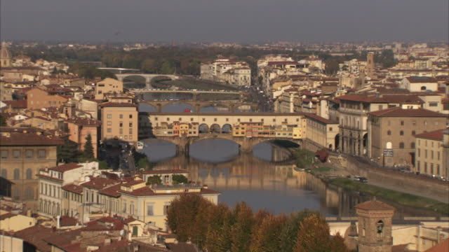 the ponte vecchio bridge spans a river in florence. available in hd. - ponte stock-videos und b-roll-filmmaterial