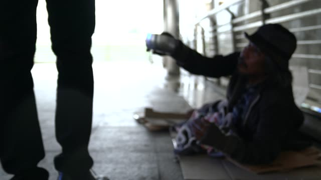 the poor homeless man or refugee sitting on the floor on the urban street in the city, social documentary concept, - beggar stock videos & royalty-free footage