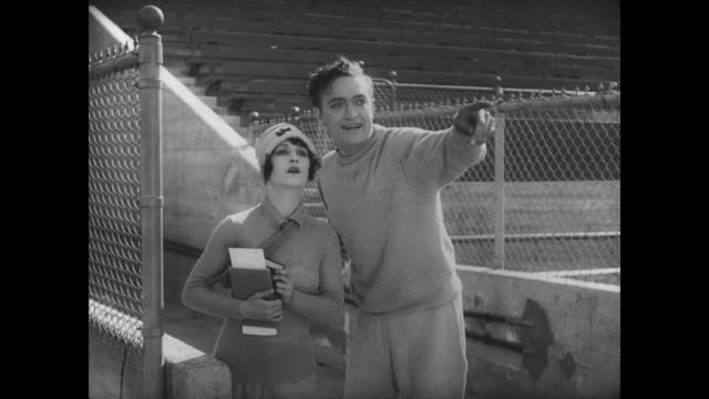 1927 the popular girl gets upset when the star athlete laughs at man's (buster keaton) inability to complete the high jump - 無声映画点の映像素材/bロール