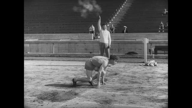 1927 the popular girl is impressed by a student's speed on the track - blocco di partenza per l'atletica video stock e b–roll