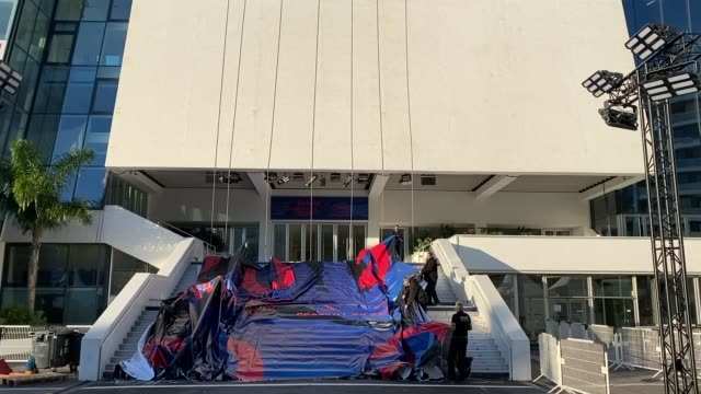the poster for the 2020 cannes film festival is put into place on the stairs above the red carpet at the palais des festivals in cannes france on... - festival poster stock videos & royalty-free footage