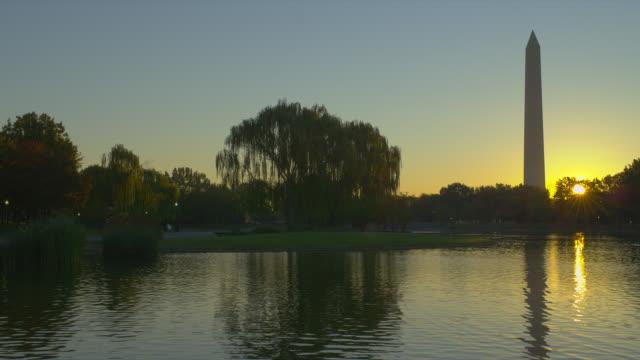 vídeos y material grabado en eventos de stock de the potomac river reflects the washington monument at sunrise. - río potomac
