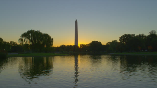 the potomac river shimmers as it reflects the washington monument at sunrise. - washington monument washington dc stock videos & royalty-free footage