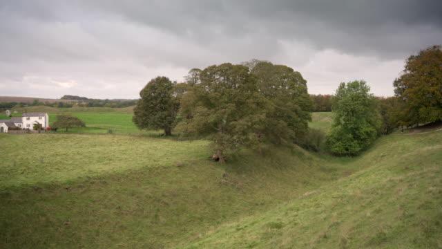 先史時代の地球は、英国ウィルトシャー州エイブベリーの石の円の周りに働きます - ウィルトシャー州点の映像素材/bロール