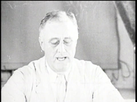 vídeos y material grabado en eventos de stock de the president sits at a desk reading a speech from a piece of paper to the camera / a family sits at home all gathered around their radio listening... - franklin roosevelt