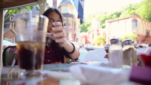 The pretty 16 years old teenager girl drinks cola in the street cafee in Jim Thorpe, Poconos region, Pennsylvania