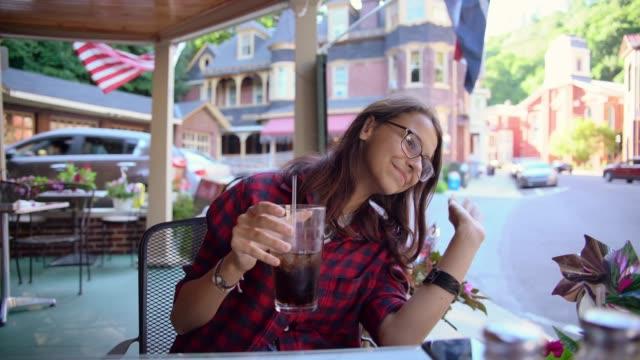 Die hübsche 16 Jahre alten Teenager-Mädchen trinkt Cola in der Straße Cafee in Jim Thorpe, Poconos Region, Pennsylvania