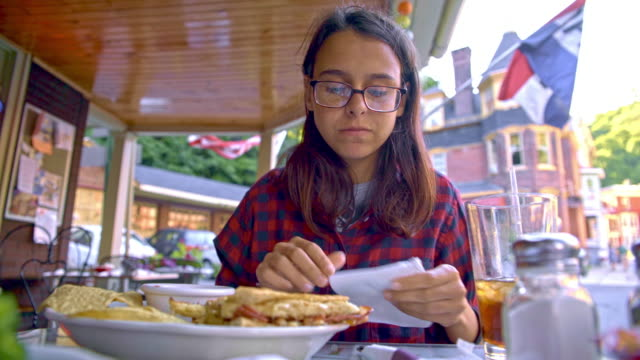 Die hübsche 16 Jahre alte Teenager Mädchen isst die Salsa mit Chips in der Straße Cafee in Jim Thorpe, Poconos Region, Pennsylvania