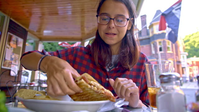 The pretty 16 years old teenager girl eats the sandvich in the street cafee in Jim Thorpe, Poconos region, Pennsylvania