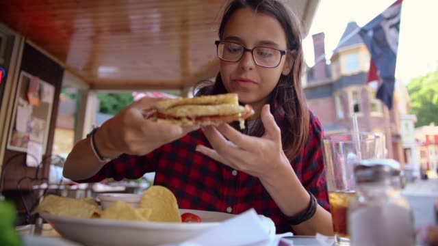 Die hübsche 16 Jahre alten Teenager Mädchen isst das Sandvich in der Straße Cafee in Jim Thorpe, Poconos Region, Pennsylvania