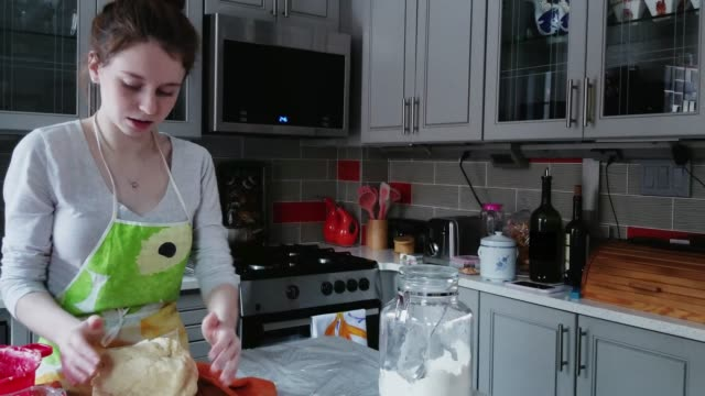 The pretty teenager girl cooking - making sweet pastries in the kitchen