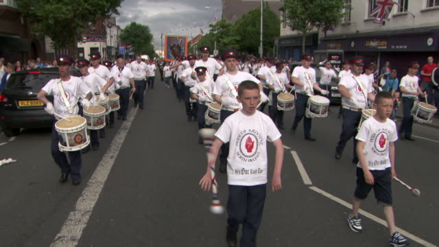 the pride of ardoyne flute band, a loyalist/unionist marching band, approaches a typically catholic area of belfast, northern ireland. - northern ireland stock videos & royalty-free footage