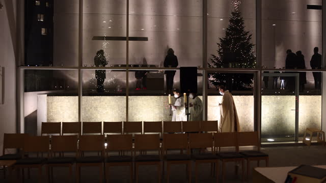 the priest and altar server wearing protective face masks open a service at st. canisius catholic church on christmas day during the second wave of... - christentum stock-videos und b-roll-filmmaterial