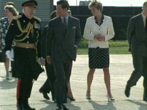 the prince and princess of wales walk across heathrow tarmac before boarding private aircraft / charles talks to officials whilst diana says little - wales stock-videos und b-roll-filmmaterial