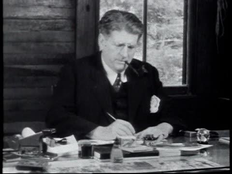 1940 MONTAGE the principal of Calhoun school working at desk / Alabama, United States